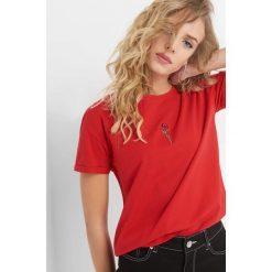 T-shirt z kwiatowym haftem. Czerwone t-shirty damskie Orsay, z haftami, z bawełny, z klasycznym kołnierzykiem. Za 29.99 zł.