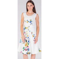 Rozkloszowana wizytowa sukienka ecru QUIOSQUE. Białe sukienki damskie QUIOSQUE, w kolorowe wzory, ze skóry ekologicznej, eleganckie, z krótkim rękawem. W wyprzedaży za 79.99 zł.