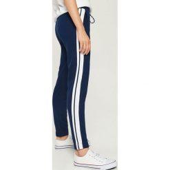 Spodnie dresowe z lampasami - Granatowy. Niebieskie spodnie dresowe damskie Sinsay, z dresówki. Za 49.99 zł.