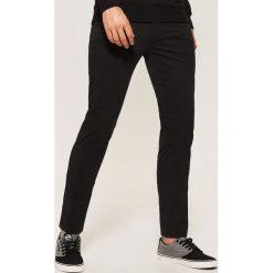 Materiałowe spodnie slim fit - Czarny. Spodnie materiałowe męskie marki House. W wyprzedaży za 59.99 zł.
