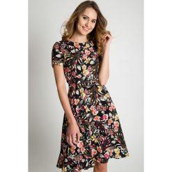 Czarna sukienka w kwiatowy wzór BIALCON. Czarne sukienki damskie BIALCON, na lato, eleganckie, z kopertowym dekoltem. Za 495.00 zł.