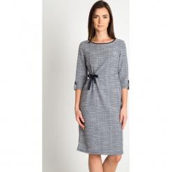 Szara melanżowa sukienka z wiązaniem QUIOSQUE. Szare sukienki damskie QUIOSQUE, melanż, z dzianiny, biznesowe, z dekoltem na plecach. W wyprzedaży za 139.99 zł.