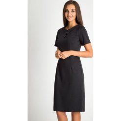 Czarna sukienka z koralikami przy dekolcie QUIOSQUE. Czarne sukienki damskie QUIOSQUE, na lato, z dzianiny, z długim rękawem. W wyprzedaży za 159.99 zł.