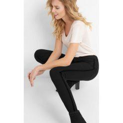 Jegginsy z welurowymi lampasami. Czarne legginsy damskie Orsay, w paski, z bawełny. Za 79.99 zł.
