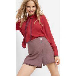 Asymetryczne spodenki. Czerwone szorty damskie Orsay, w geometryczne wzory, z elastanu. W wyprzedaży za 50.00 zł.