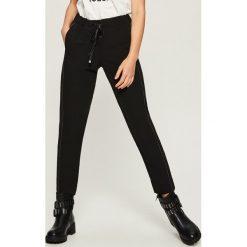 Spodnie dresowe z aplikacją - Czarny. Czarne spodnie dresowe damskie Sinsay, z aplikacjami, z dresówki. Za 79.99 zł.