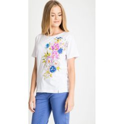 Biała bawełniana bluzka z kwiatami QUIOSQUE. Białe bluzki damskie QUIOSQUE, z nadrukiem, z bawełny, biznesowe, z okrągłym kołnierzem, z krótkim rękawem. W wyprzedaży za 29.99 zł.