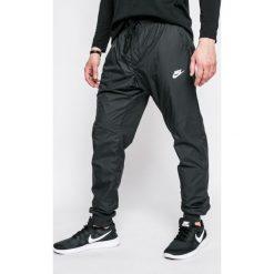 Nike Sportswear - Spodnie. Szare spodnie sportowe męskie Nike Sportswear, z aplikacjami, z poliesteru. W wyprzedaży za 219.90 zł.
