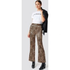 NA-KD Trend Spodnie Flared Shiny Leo - Brown. Brązowe spodnie materiałowe damskie NA-KD Trend, z materiału. Za 141.95 zł.
