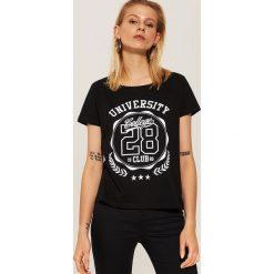 T-shirt z nadrukiem University - Czarny. T-shirty damskie marki DOMYOS. W wyprzedaży za 19.99 zł.