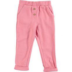 Spodnie dresowe w kolorze jasnoróżowym. Spodenki niemowlęce marki 4f. W wyprzedaży za 32.95 zł.