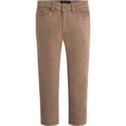 Spodnie w kolorze jasnobrązowym. Brązowe spodnie materiałowe dla chłopców marki Mayoral, w paski. W wyprzedaży za 89.95 zł.