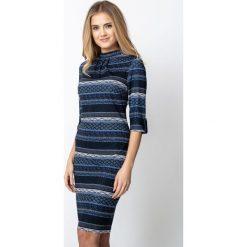 Wzorzysta sukienka ze stójką QUIOSQUE. Brązowe sukienki damskie QUIOSQUE, na zimę, z dzianiny, z dekoltem na plecach, z długim rękawem. Za 199.99 zł.