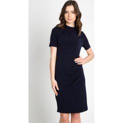 Granatowa sukienka z marszczeniem QUIOSQUE. Szare sukienki damskie QUIOSQUE, ze stójką, z krótkim rękawem. W wyprzedaży za 99.99 zł.