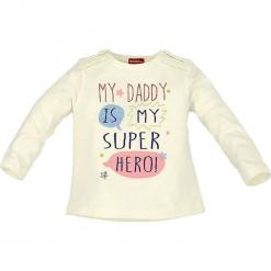 """Koszulka """"Super Hero"""" w kolorze białym. Białe bluzki dla dziewczynek Bondi, z nadrukiem, z bawełny, z falbankami, z długim rękawem. W wyprzedaży za 32.95 zł."""