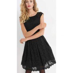 Koronkowa sukienka z brokatem. Czarne sukienki damskie Orsay, w koronkowe wzory, z elastanu, wizytowe, z okrągłym kołnierzem. Za 179.99 zł.