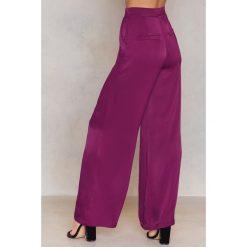 NA-KD Błyszczące spodnie z rozszerzanymi nogawkami - Purple. Fioletowe spodnie materiałowe damskie NA-KD, z wiskozy. W wyprzedaży za 60.89 zł.