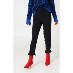 NA-KD Spodnie wykończone falbaną na nogawce - Black. Czarne spodnie materiałowe damskie NA-KD, z poliesteru. Za 161.95 zł.