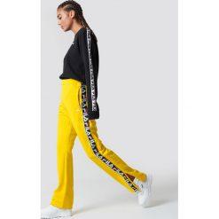 FILA Spodnie Thora Track - Yellow. Żółte spodnie materiałowe damskie Fila, w paski. Za 283.95 zł.