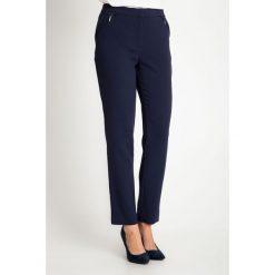 Granatowe eleganckie spodnie z kieszeniami na biodrach QUIOSQUE. Szare spodnie materiałowe damskie QUIOSQUE, z haftami, z tkaniny. W wyprzedaży za 159.99 zł.