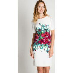 Klasyczna biała sukienka z kwiatową aplikacją BIALCON. Białe sukienki damskie BIALCON, z aplikacjami, klasyczne, z kopertowym dekoltem. Za 335.00 zł.