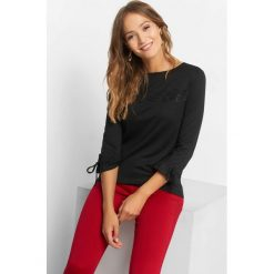 Koszulka z koronkową wstawką. Czarne bluzki damskie Orsay, w jednolite wzory, z dzianiny, z falbankami, z długim rękawem. Za 69.99 zł.
