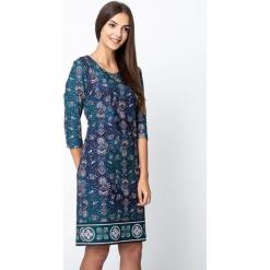 Zielona sukienka z etnicznym wzorem QUIOSQUE. Zielone sukienki damskie QUIOSQUE, z dzianiny, klasyczne, z dekoltem na plecach, z długim rękawem. Za 199.99 zł.