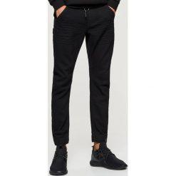 Jeansy SLIM JOGGER - Czarny. Czarne jeansy męskie Cropp. Za 119.99 zł.