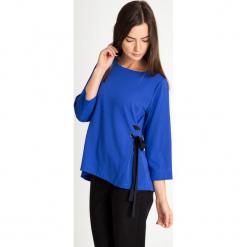 Kobaltowa bluzka z bocznym wiązaniem QUIOSQUE. Niebieskie bluzki damskie QUIOSQUE, w ażurowe wzory, ze skóry ekologicznej, klasyczne, z kopertowym dekoltem, z krótkim rękawem. W wyprzedaży za 99.99 zł.