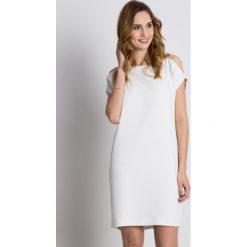 Luźna sukienka z odkrytymi ramionami i łańcuszkiem BIALCON. Sukienki damskie BIALCON, na lato, z tkaniny, eleganckie, z kopertowym dekoltem. Za 295.00 zł.