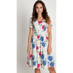 Rozkloszowana biała sukienka w kwiaty BIALCON. Białe sukienki damskie BIALCON, w kwiaty, wizytowe, z okrągłym kołnierzem. W wyprzedaży za 200.00 zł.