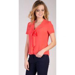 Malinowa bluzka z wiązaniem na dekolcie  QUIOSQUE. Bluzki damskie QUIOSQUE, z tkaniny, biznesowe, z kokardą, z krótkim rękawem. W wyprzedaży za 49.99 zł.