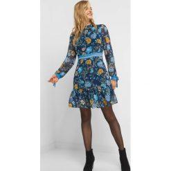 Szyfonowa sukienka w kwiaty. Niebieskie sukienki damskie Orsay, w kwiaty, z dzianiny, z dekoltem na plecach, z długim rękawem. Za 139.99 zł.