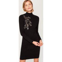 Dopasowana sukienka z połyskującą aplikacją - Czarny. Czarne sukienki damskie Mohito, z aplikacjami. Za 159.99 zł.