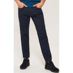 Materiałowe spodnie slim fit - Granatowy. Spodnie materiałowe męskie marki House. W wyprzedaży za 59.99 zł.