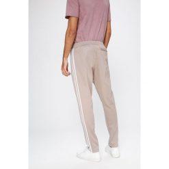Adidas Originals - Spodnie. Szare spodnie sportowe męskie adidas Originals, z bawełny. W wyprzedaży za 239.90 zł.