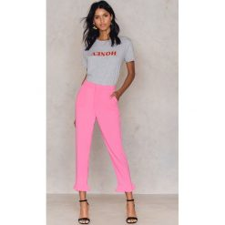 NA-KD Spodnie wykończone falbaną na nogawce - Pink. Różowe spodnie materiałowe damskie NA-KD, z poliesteru. Za 161.95 zł.