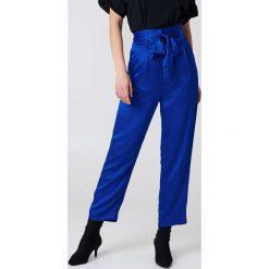NA-KD Party Satynowe spodnie z wiązaniem w talii - Blue. Niebieskie spodnie materiałowe damskie NA-KD Party, z haftami, z satyny. Za 80.95 zł.