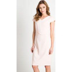 Jasnoróżowa sukienka z kokardą QUIOSQUE. Białe sukienki damskie QUIOSQUE, na lato, w paski, z satyny, eleganckie, z kopertowym dekoltem. W wyprzedaży za 99.99 zł.