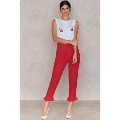 NA-KD Spodnie wykończone falbaną na nogawce - Red. Czerwone spodnie materiałowe damskie NA-KD. Za 161.95 zł.