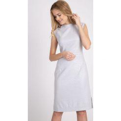 Błyszcząca szara sukienka z rozporkiem QUIOSQUE. Szare sukienki damskie QUIOSQUE, w geometryczne wzory, z dzianiny, eleganckie, z kopertowym dekoltem, bez rękawów. W wyprzedaży za 79.99 zł.