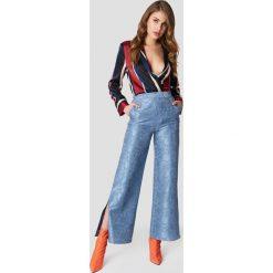 NA-KD Spodnie dzwony z kwiatowym motywem - Blue. Niebieskie spodnie materiałowe damskie NA-KD, z poliesteru. W wyprzedaży za 80.98 zł.