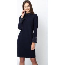 Granatowa sukienka z koralikami QUIOSQUE. Szare sukienki damskie QUIOSQUE, z aplikacjami, z tkaniny, biznesowe, z kopertowym dekoltem, z długim rękawem. Za 239.99 zł.