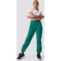NA-KD Trend Spodnie Side Stripe Tracksuit - Green. Zielone spodnie materiałowe damskie NA-KD Trend, w paski. Za 141.95 zł.