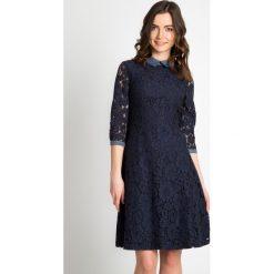Granatowa koronkowa sukienka QUIOSQUE. Szare sukienki damskie QUIOSQUE, w koronkowe wzory, z jeansu, biznesowe, z kopertowym dekoltem, z długim rękawem. W wyprzedaży za 109.99 zł.