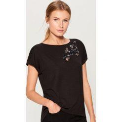 Koszulka z aplikacją - Czarny. Czarne t-shirty damskie Mohito, z aplikacjami. W wyprzedaży za 39.99 zł.
