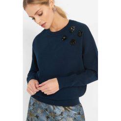 Sweter z aplikacją 3D. Niebieskie swetry damskie Orsay, z dzianiny, z okrągłym kołnierzem. Za 99.99 zł.