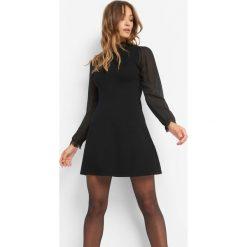 Sukienka z balonowymi rękawami. Czarne sukienki damskie Orsay, z dzianiny, ze stójką. Za 119.99 zł.