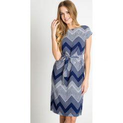Granatowa wiązana sukienka w geometryczny wzór QUIOSQUE. Białe sukienki damskie QUIOSQUE, w geometryczne wzory, z wiskozy, wakacyjne, z krótkim rękawem. W wyprzedaży za 99.99 zł.