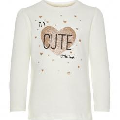 """Koszulka """"Rastar"""" w kolorze białym. Białe bluzki dla dziewczynek Name it Kids, z nadrukiem, z bawełny, z okrągłym kołnierzem, z długim rękawem. W wyprzedaży za 25.95 zł."""